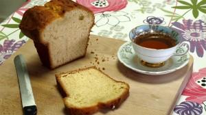 Houten broodplank met aangesneden citroencake en een kopje thee