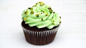 Pistachecupcake met groene topping en stukjes noot