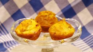 Hartige muffins met kip en mais op een glazen schaal voor een blauwgeblokte theedoek