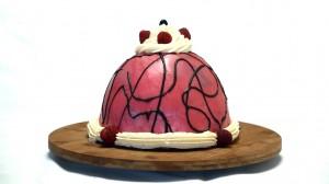 Frambozenboltaart op een houten plank met roze botercreme en chocoladedecoratie