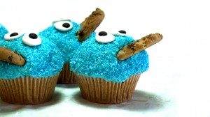 Vier blauwe koekiemonstercupcakes met blauwe kokos en koekjes